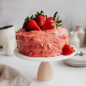 A pink strawberry cake frosted with strawberry frosting on a white cake stand