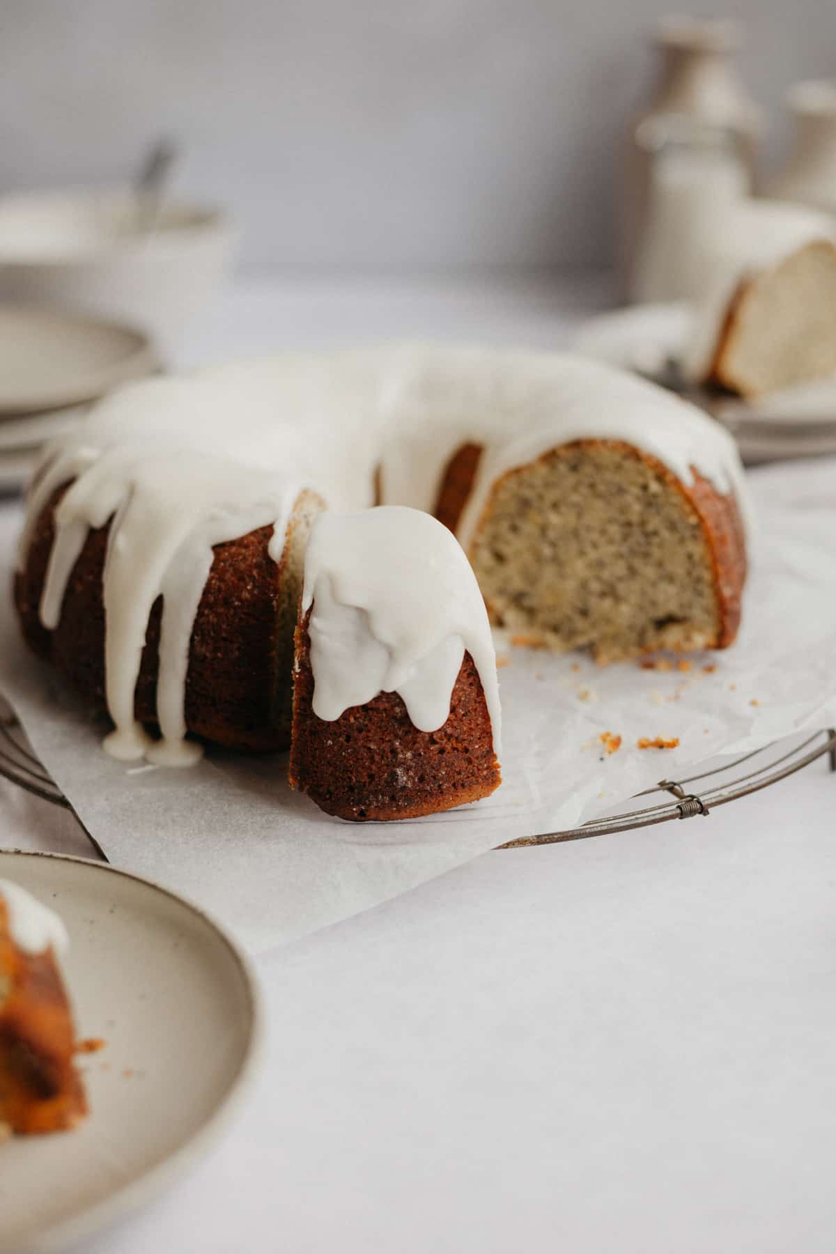 A lemon poppy seed cake with a lemon glaze drizzled on top, several slices have been taken out.