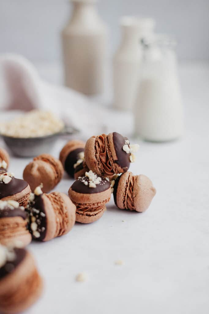 six nutella macarons on a marble counter, there is a small milk jug behind