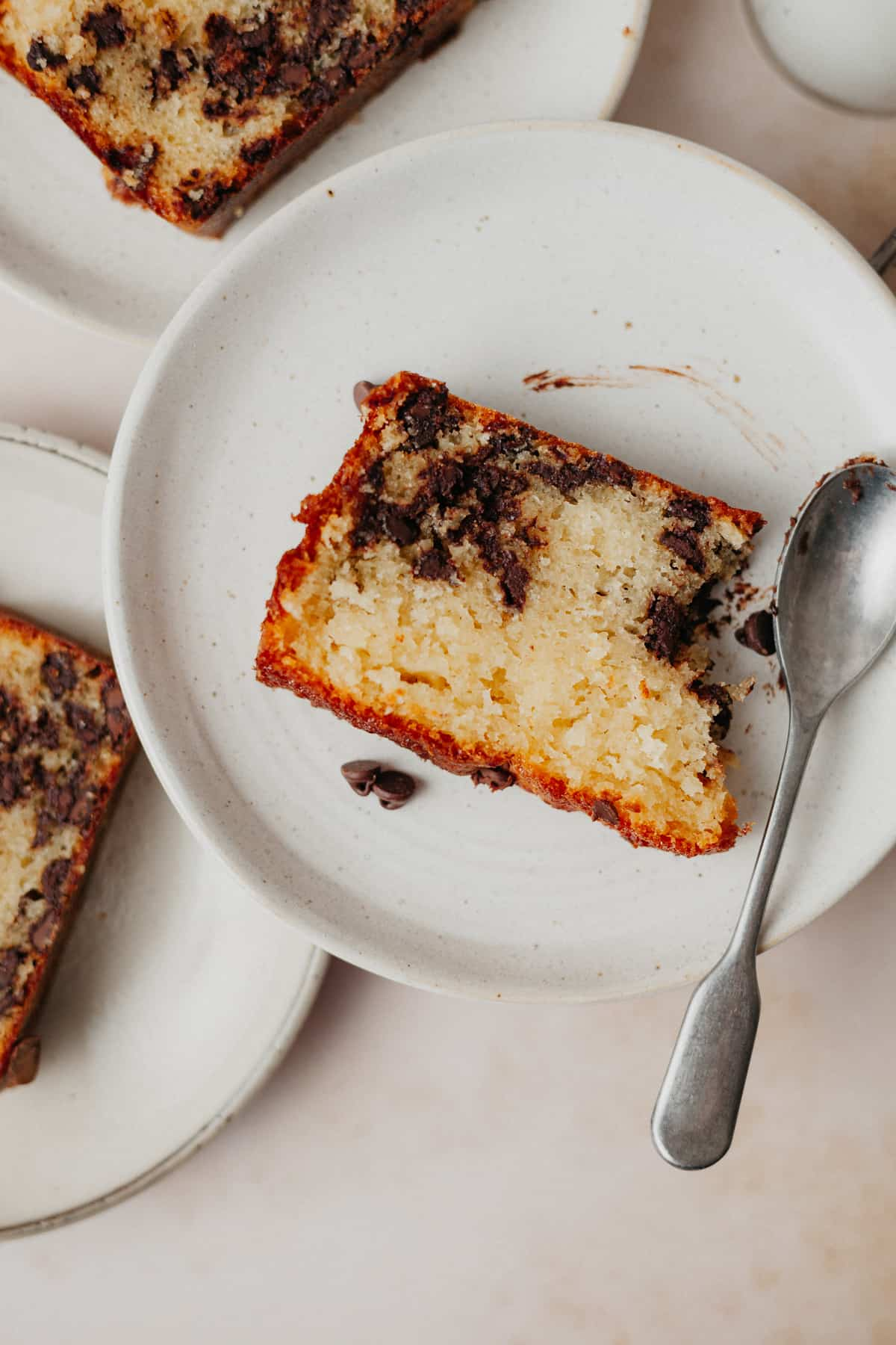 A slice of chocolate chip loaf on a small beige plate. There is a small silver spoon