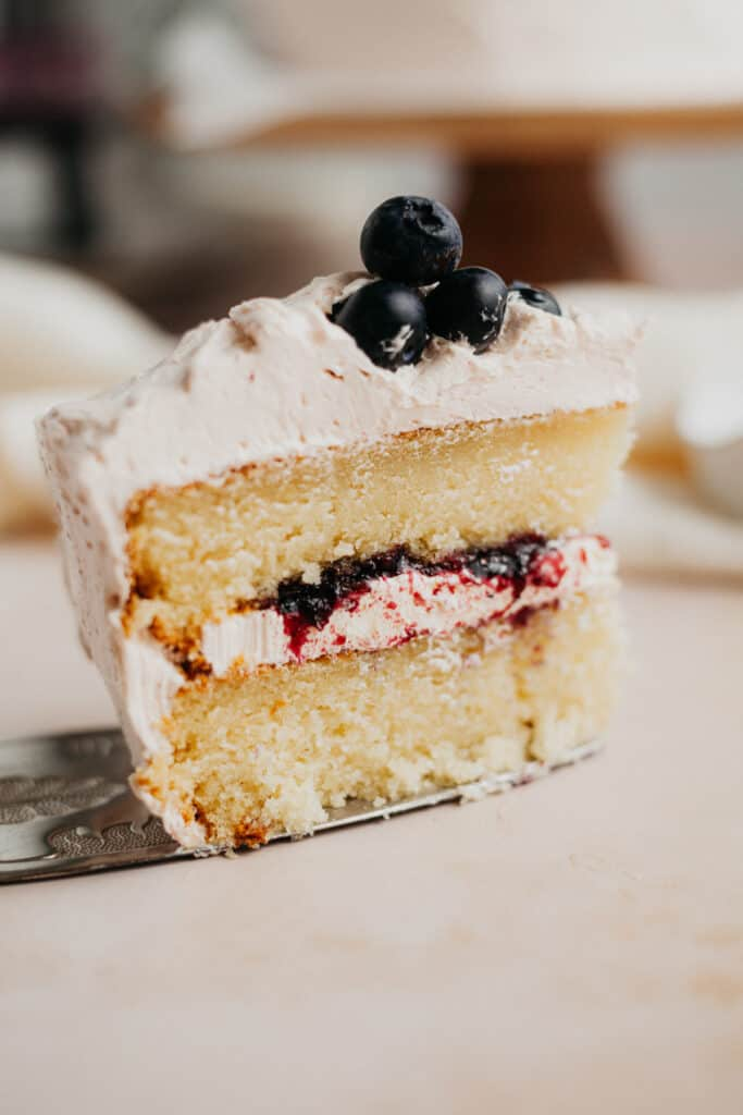 A slice of blueberry jam cake on a silver cake server