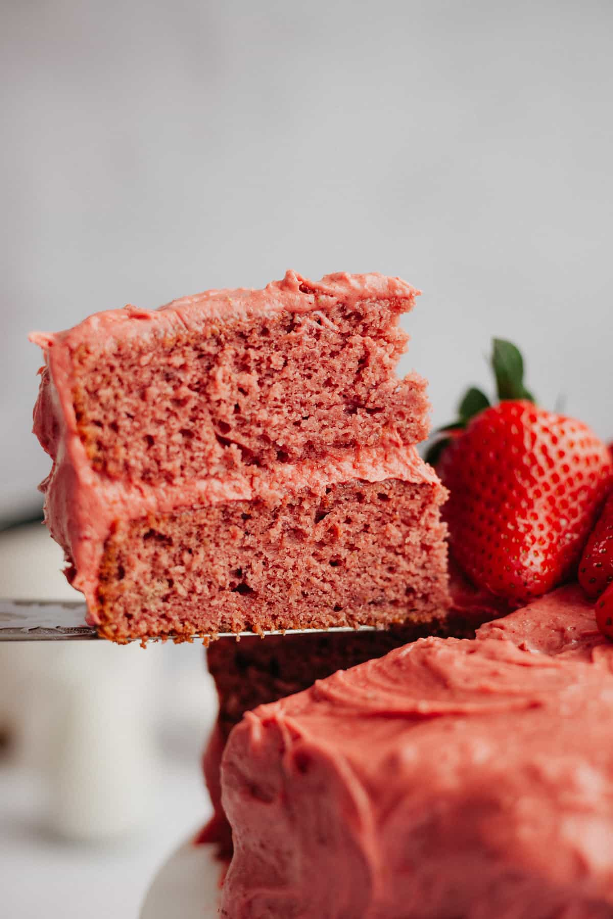 A close up of a slice of strawberry cake being lifted up