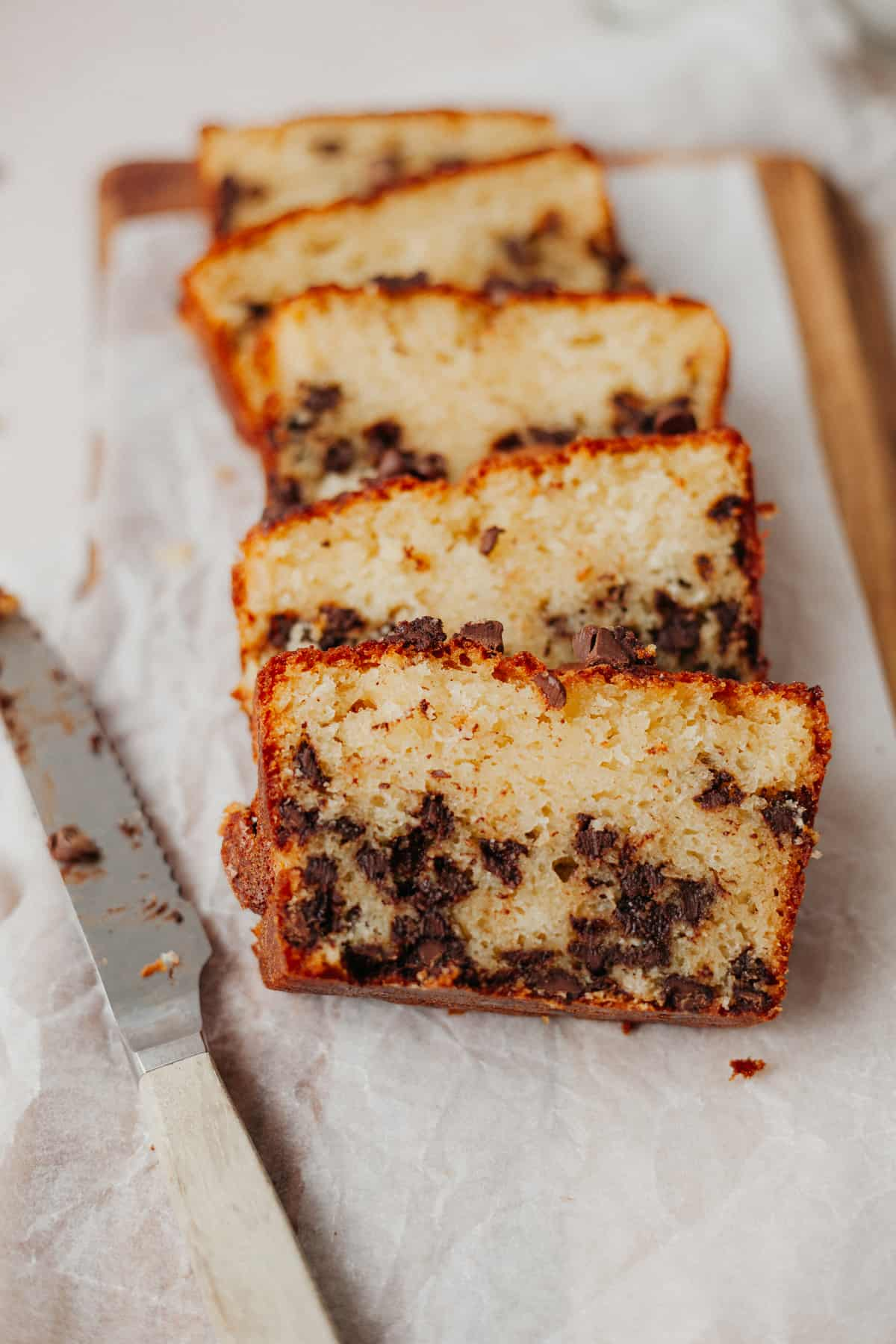 Five slices of a pound cake studded with chocolate chips on white parchment paper.