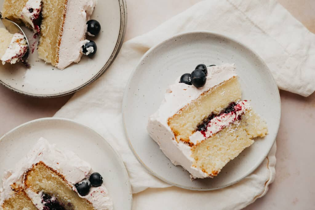 Three slices of blueberry jam cake on small beige plates