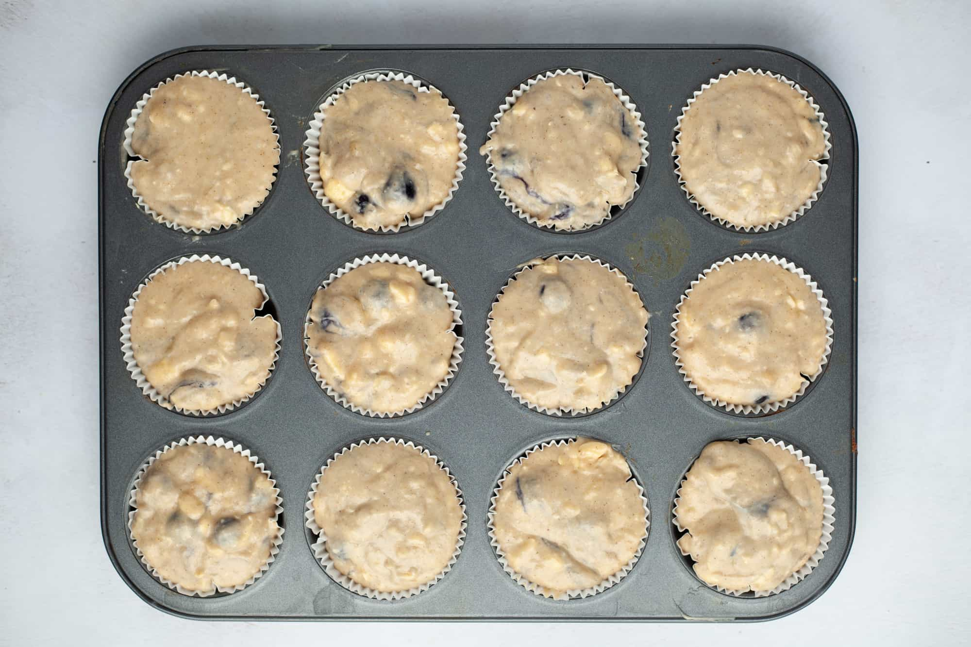 Overhead shot of muffin pan filled with unbaked muffin batter