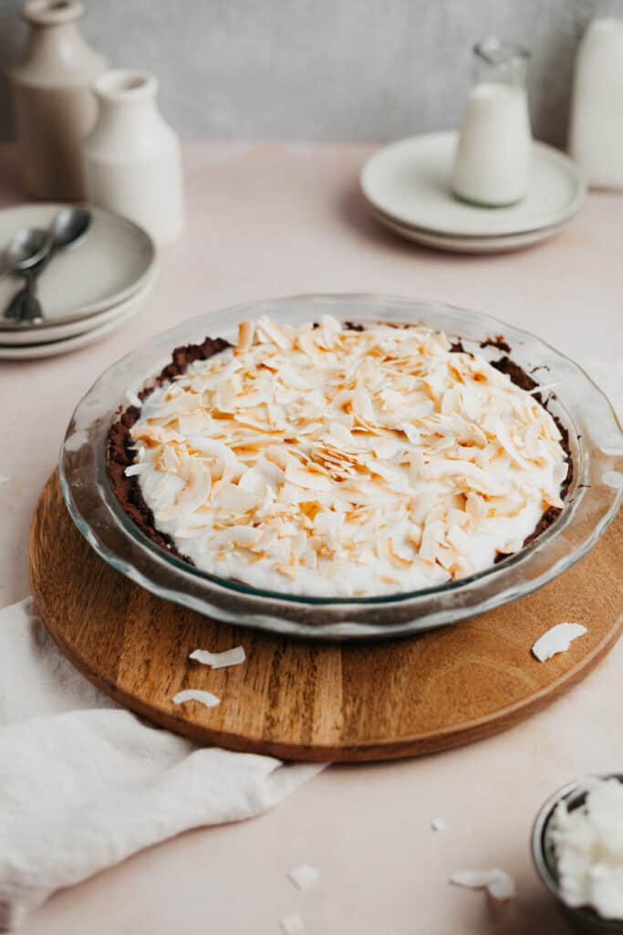 A chocolate pie topped with whipped cream and toasted coconut in a pyrex pie plate.