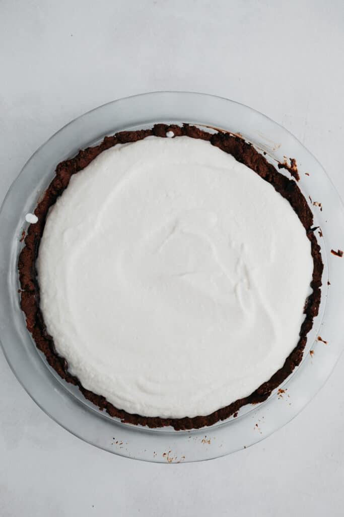 A pyrex pie plate with a chocolate cookie crust. It is covered in white coconut whipped cream