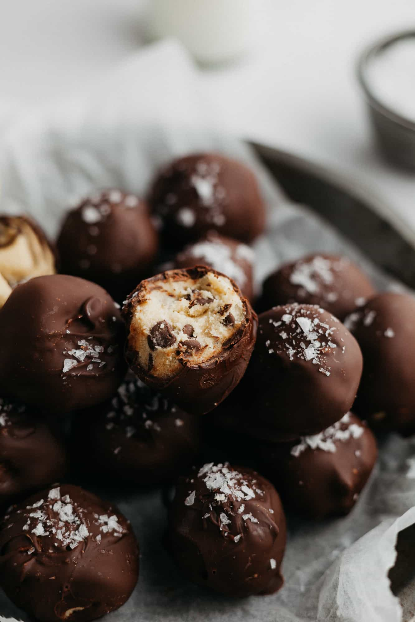 Cookie dough bites dipped in chocolate and sprinkled with sea salt on parchment paper. One has a taken out of it