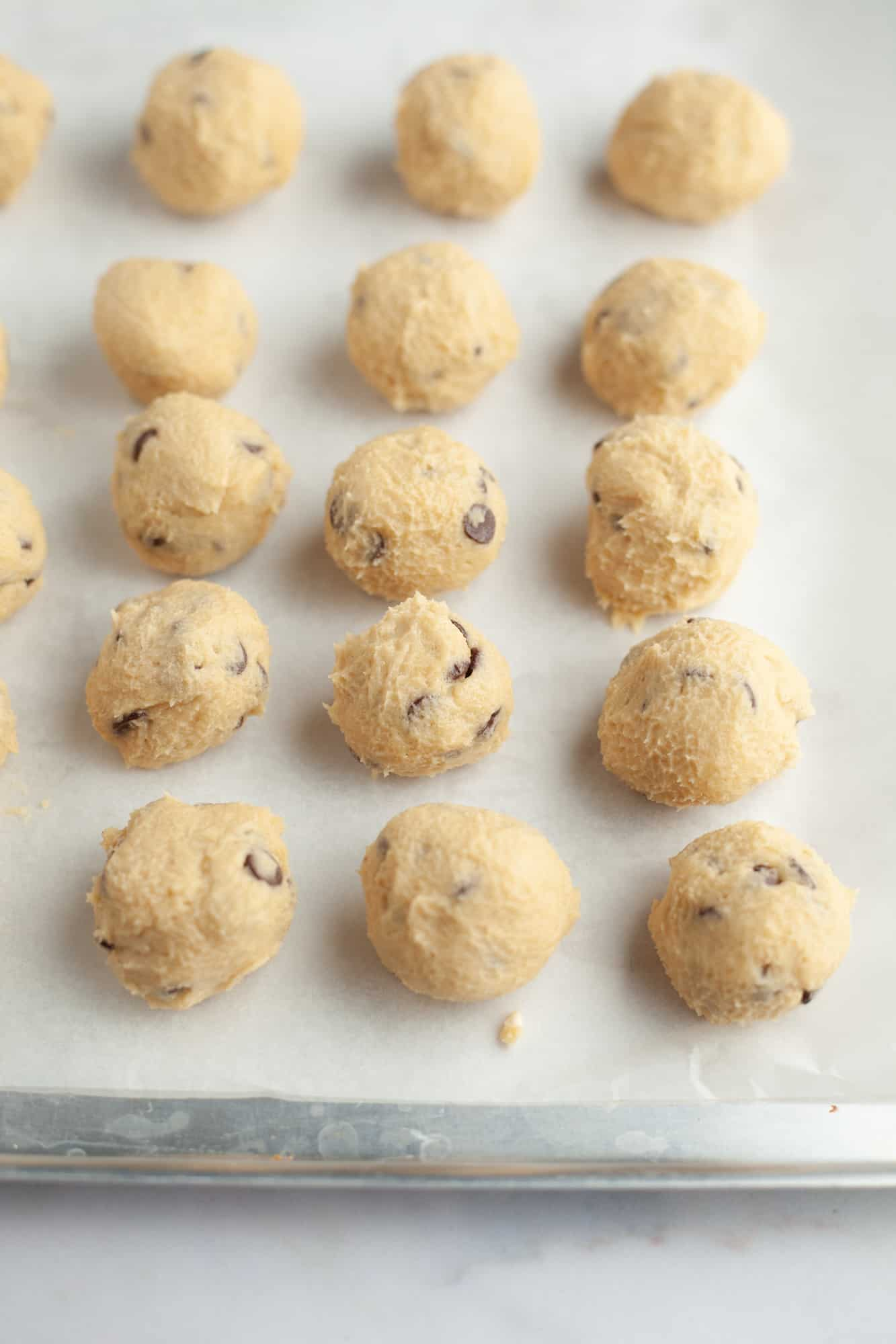 Cookie dough balls on parchment paper on a baking tray
