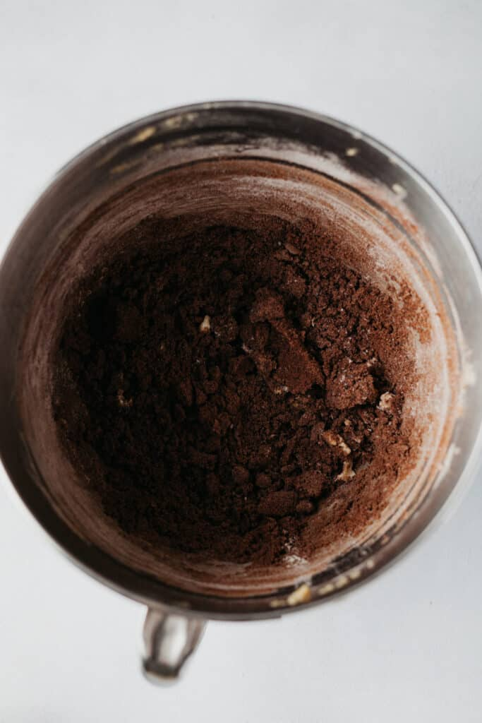 Chocolate press in cookie dough batter in a large silver mixing bowl