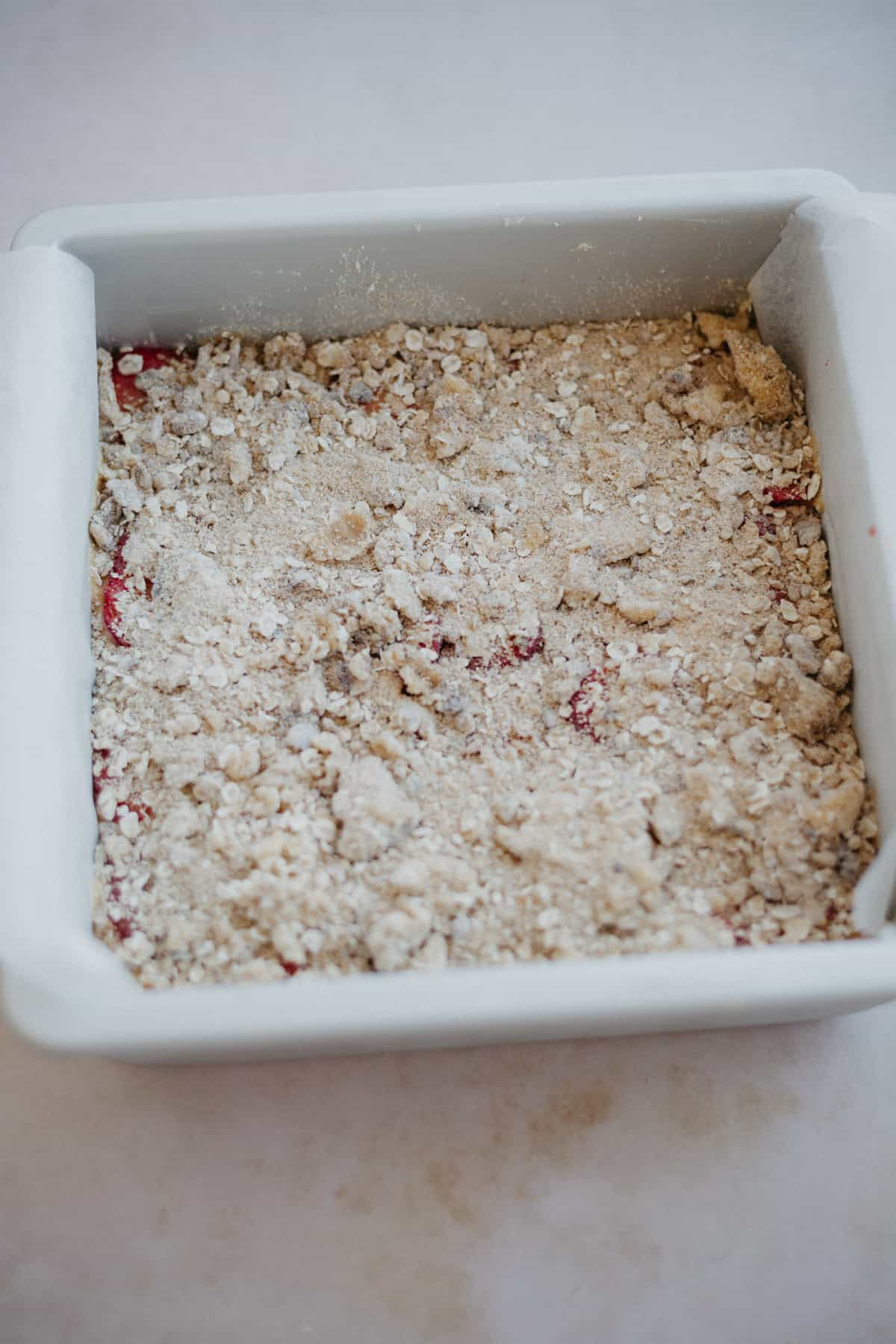 A cake pan filled with cake batter then covered in an oat crumble topping