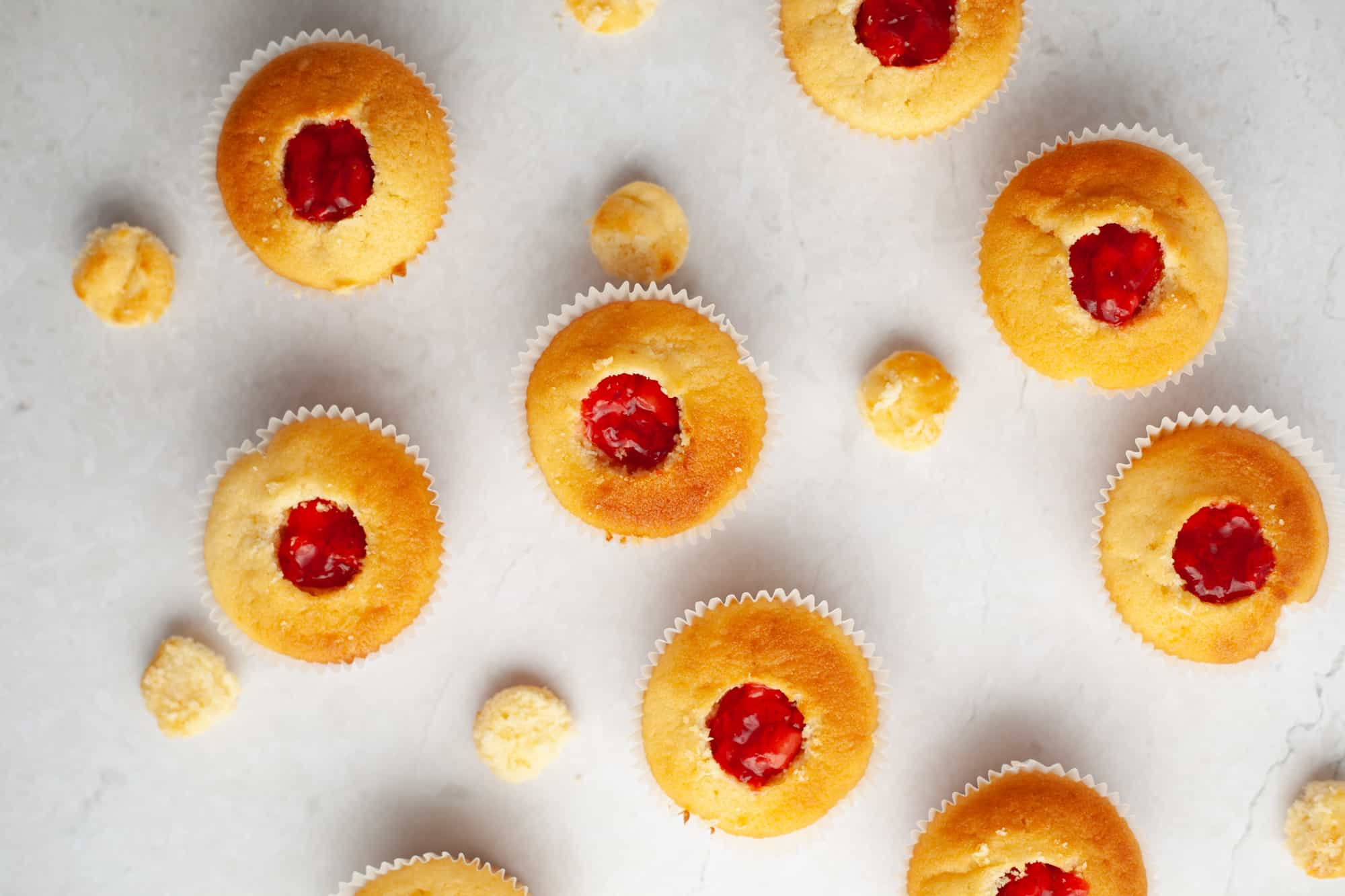 about seven yellow cupcakes, each has had a circle cut out and is filled with strawberry preserves