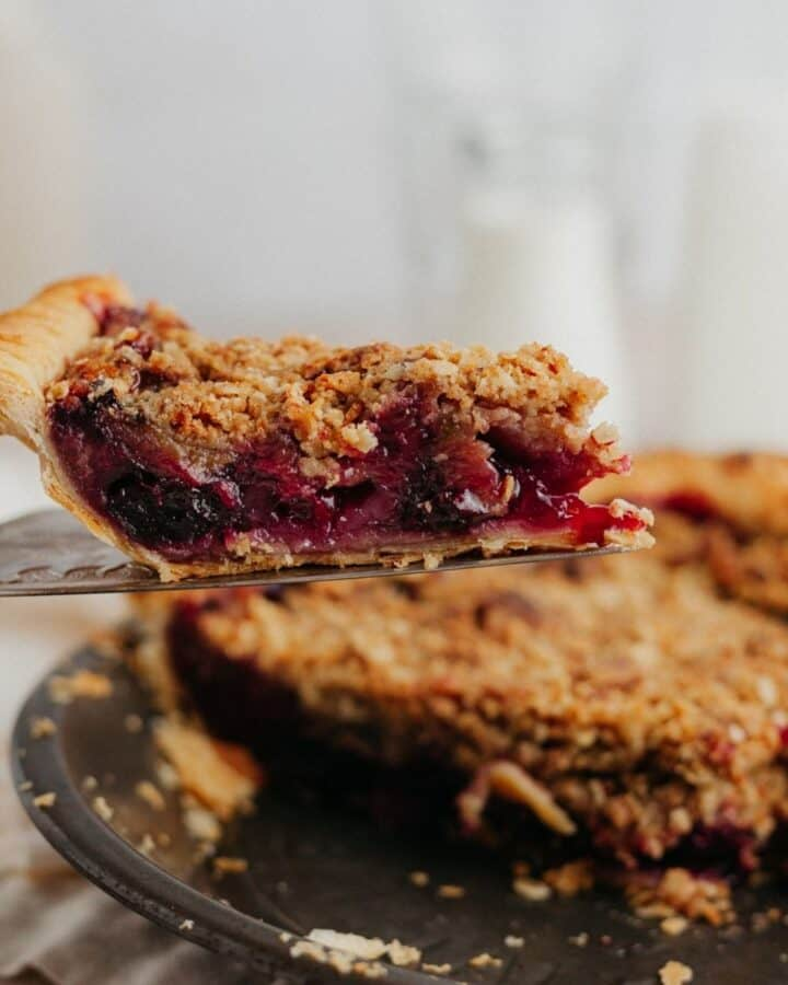 A slice of cherry and rhubarb pie being lifted out of the pie plate