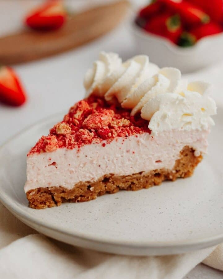 A slice of strawberry cheesecake with a whipped cream topping on a small beige plate. You can see strawberries in a ceramic bowl in the background