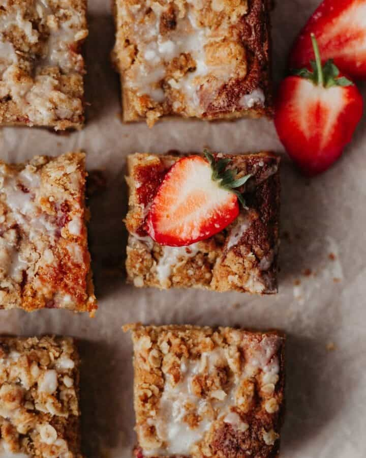 An overhead shot of squares of strawberry crumble cake. One square has a strawberry on top that has been cut in half