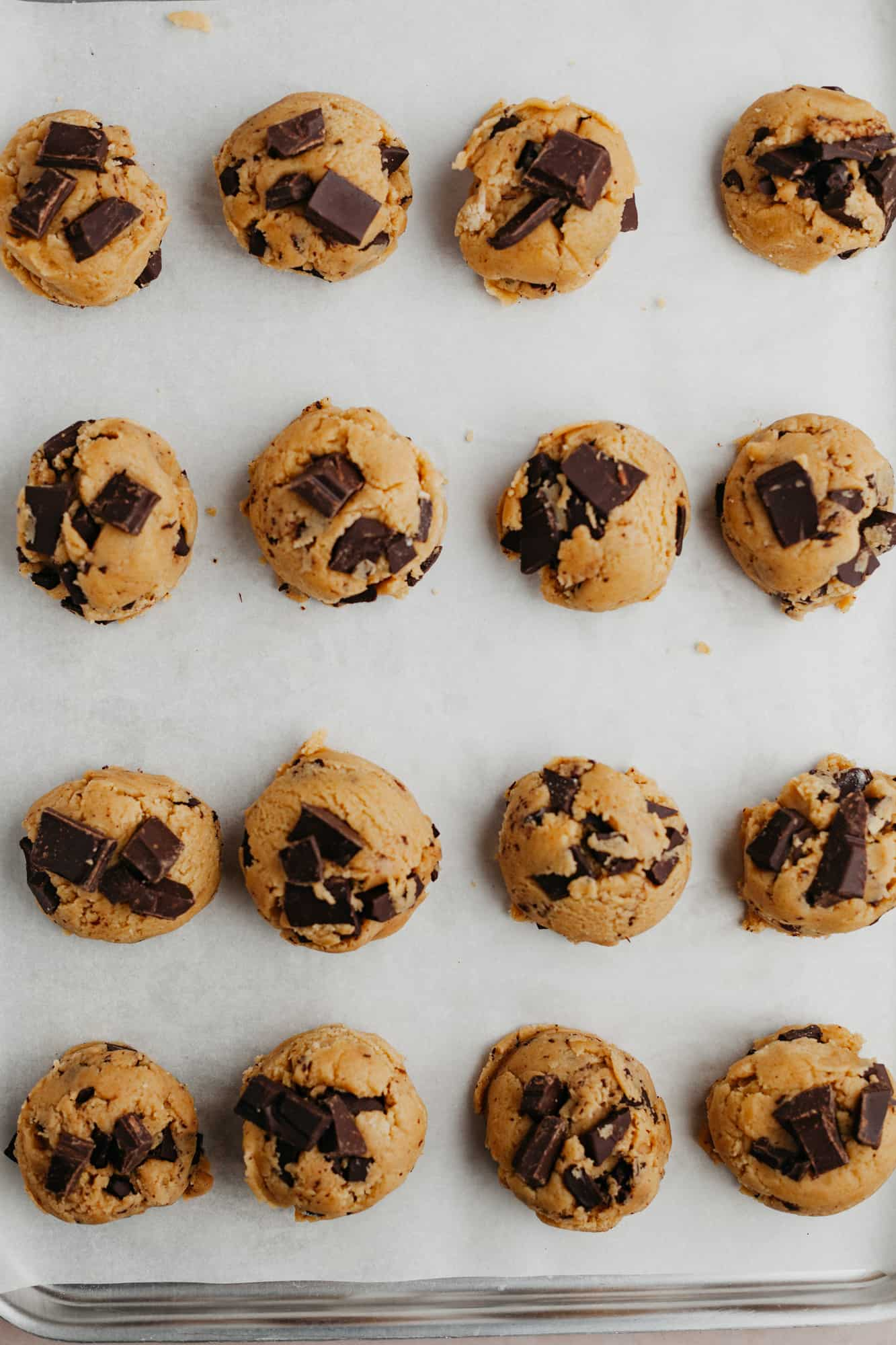 Unbaked cookie dough that has been scooped on to parchment paper