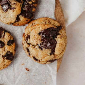 A close up of three chocolate chip cookies. The cookies are on top of parchment paper which is on top of a wooden circular board.