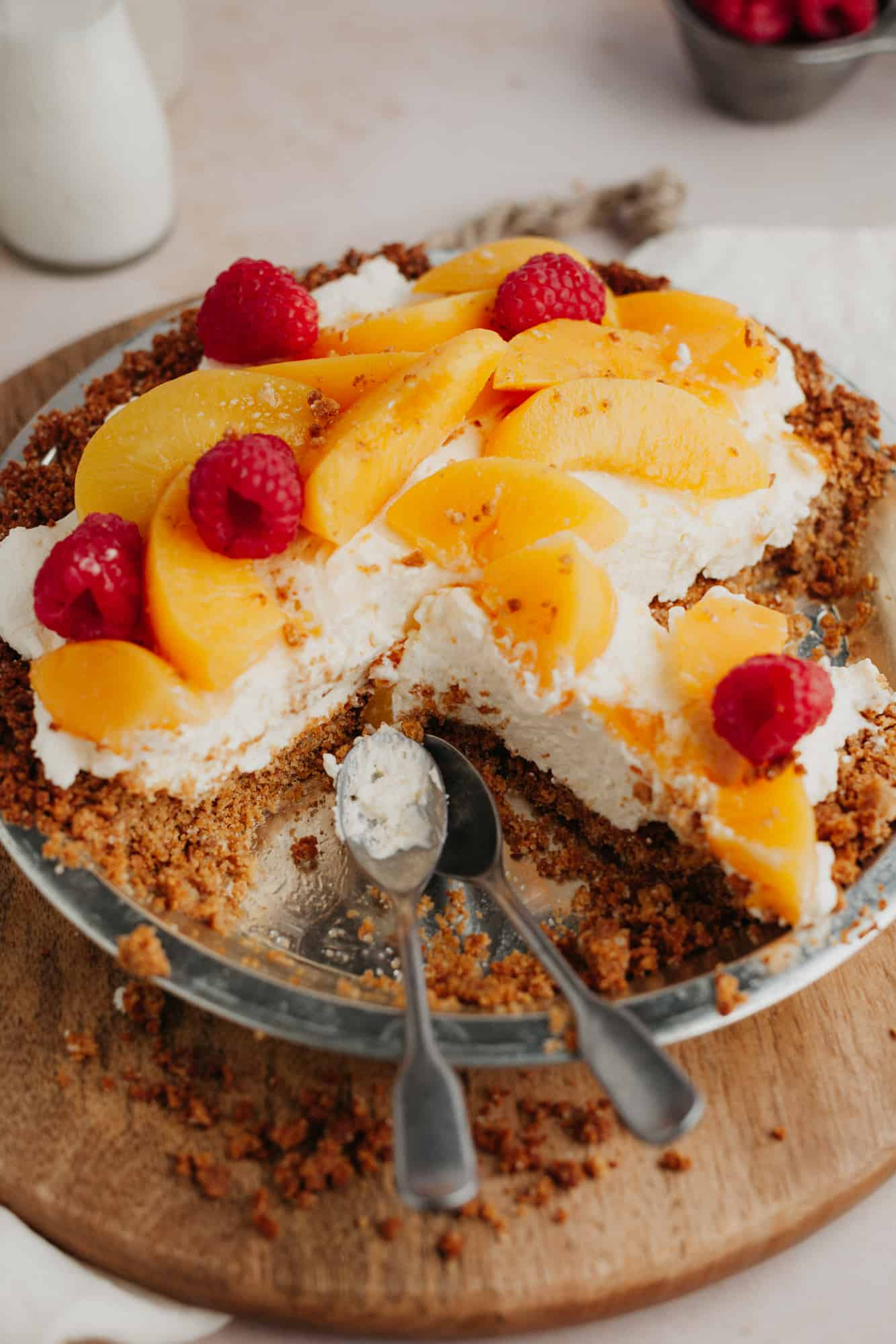 A no bake peach pie in a graham cracker crust, topped with sliced peached and raspberries. A few slices have been taken out.