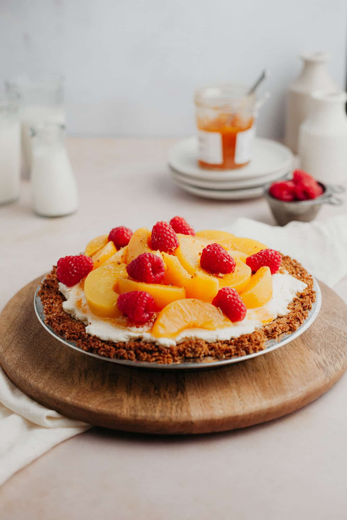 A no bake peach pie in a graham cracker crust, topped with sliced peached and raspberries. The pie plate is on a wooden circular board.