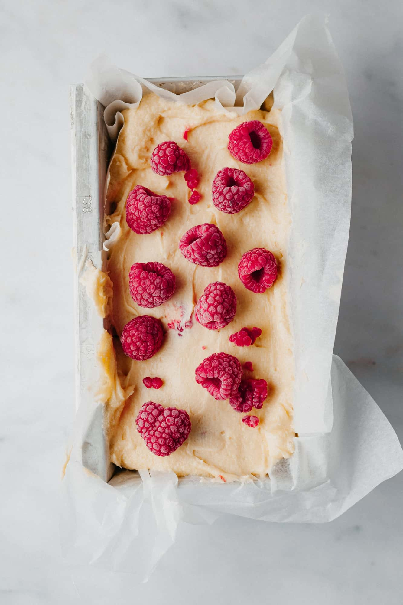 An overhead shot of unbaked cake batter in a loaf pan, topped with frozen raspberries