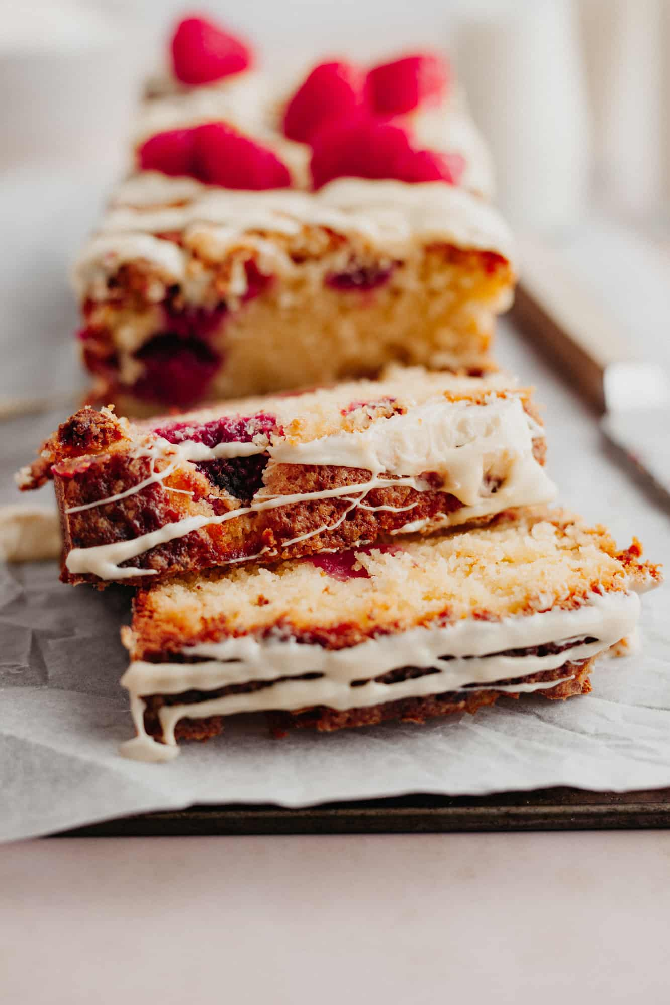 Two slices of a raspberry white chocolate loaf that have been cut.