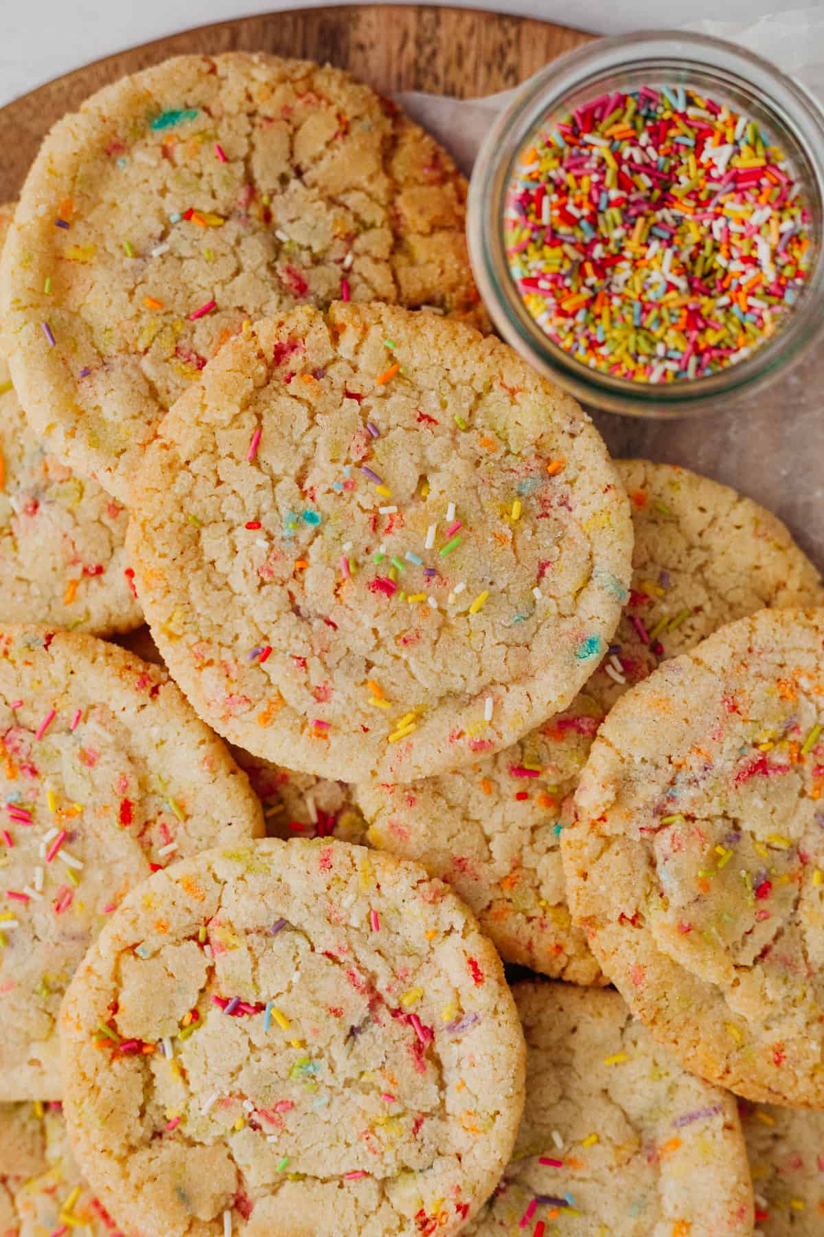 An overhead shot of sprinkle sugar cookies on a circular wooden board. There is a small glass jar full of sprinkles.