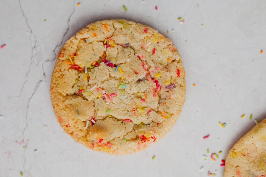A sprinkle sugar cookie on a marble counter