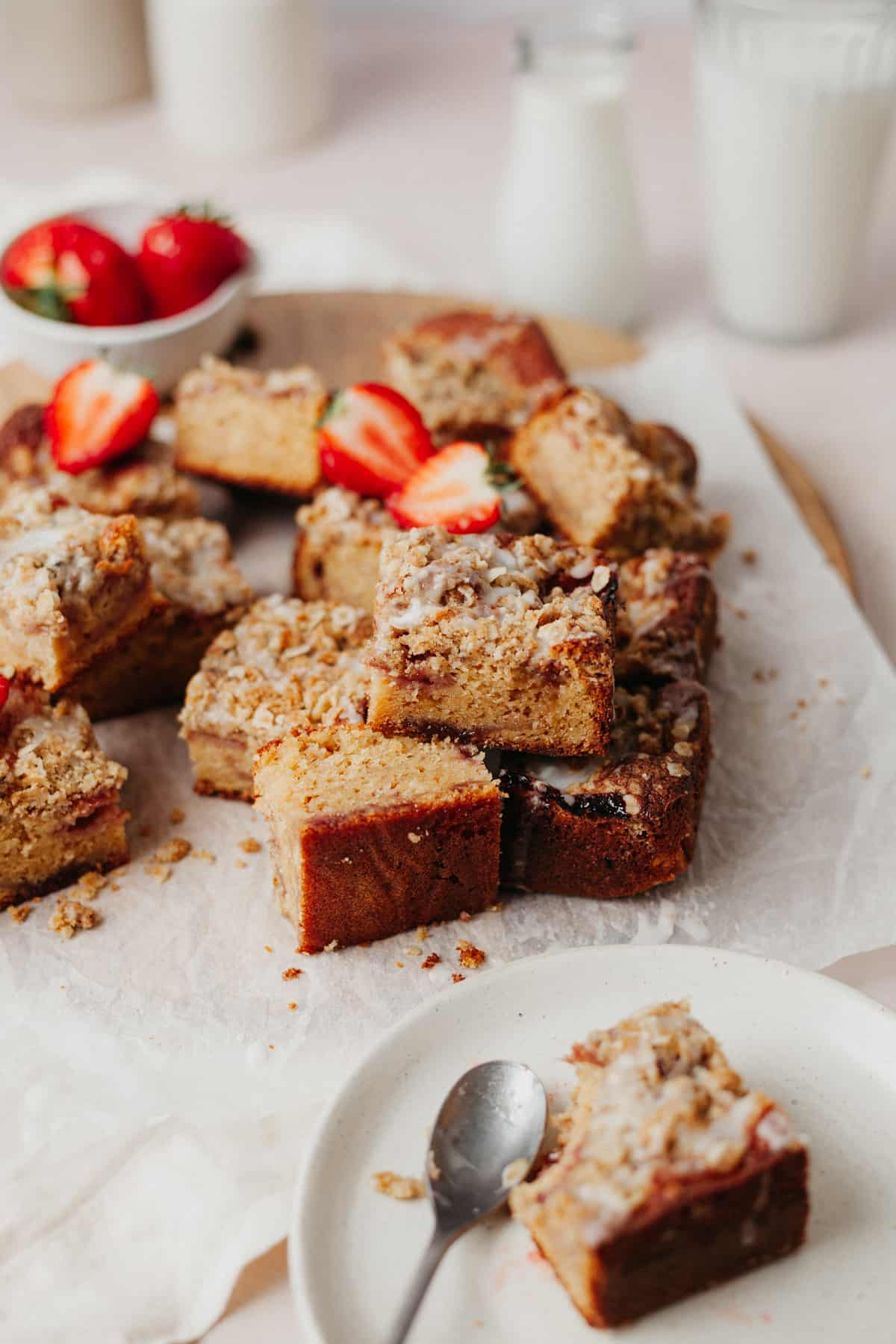 An overhead shot of squares of strawberry crumble cake. One square has a strawberry on top that has been cut in half. The slices are on top of parchment paper and there is a small plate with one slice on it