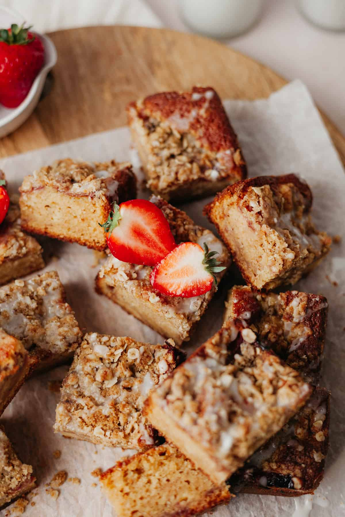 Squares of strawberry crumble cake on top of parchment paper. One square has a strawberry on top, which had been sliced in half.