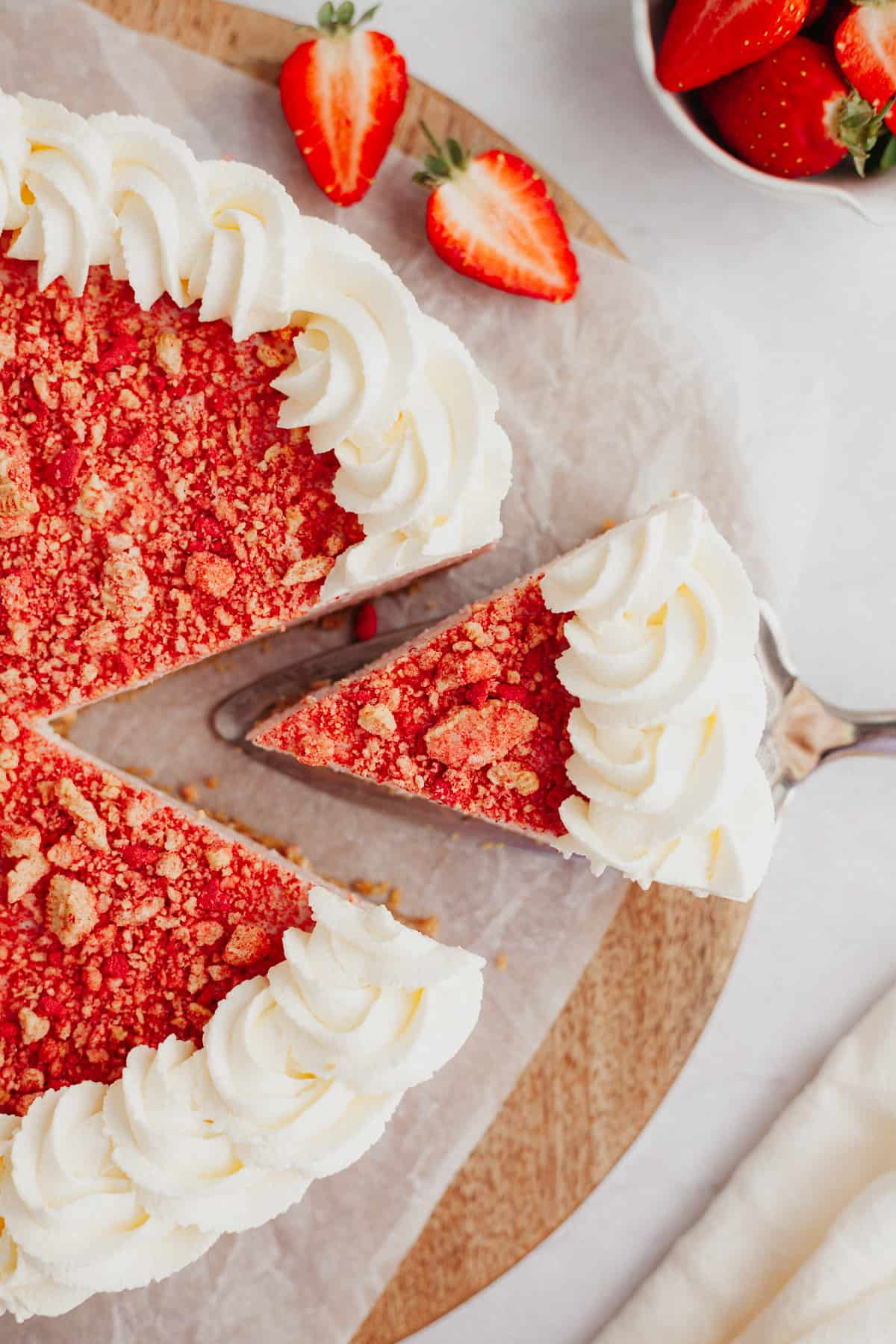 An overhead shot of a slice of strawberry cheesecake being lifted out with a silver cake server. The cheesecake has a ring of whipped cream on the outside, and then top of the cheesecake is covered in an oreo and strawberry topping.