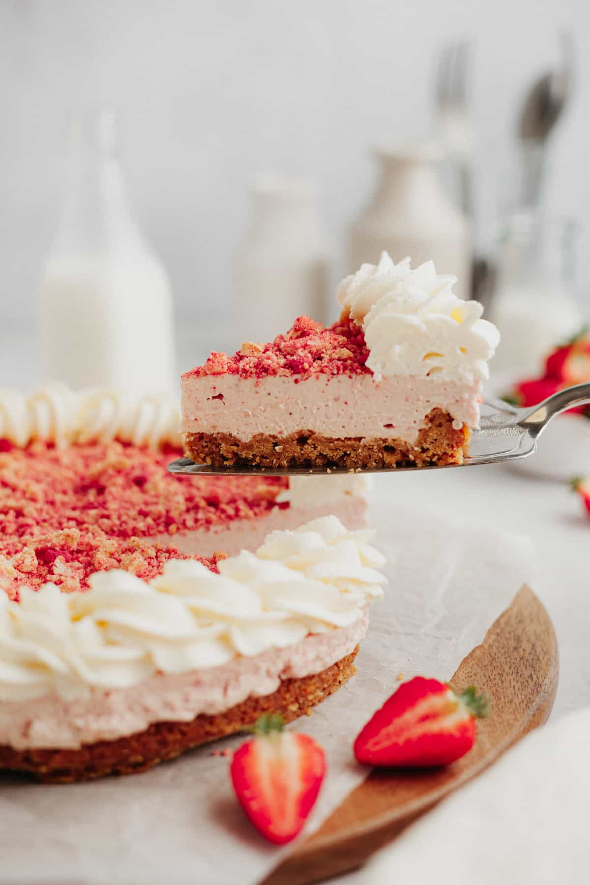 A slice of strawberry crunch cheesecake being lifted out with a silver cake server. The cheesecake is on a wooden platter.