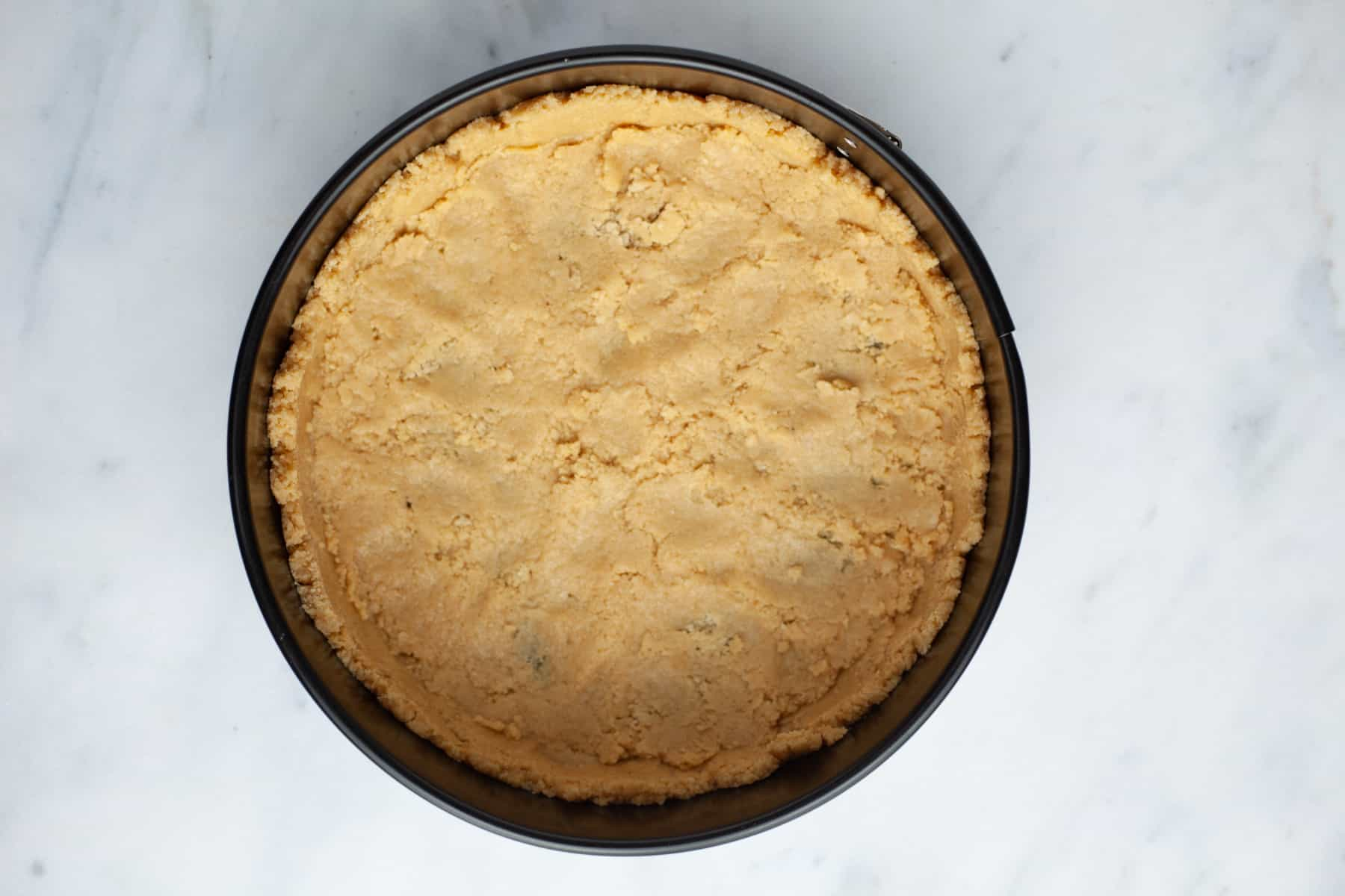 A cheesecake pan with unbaked golden oreo cheesecake crust in it