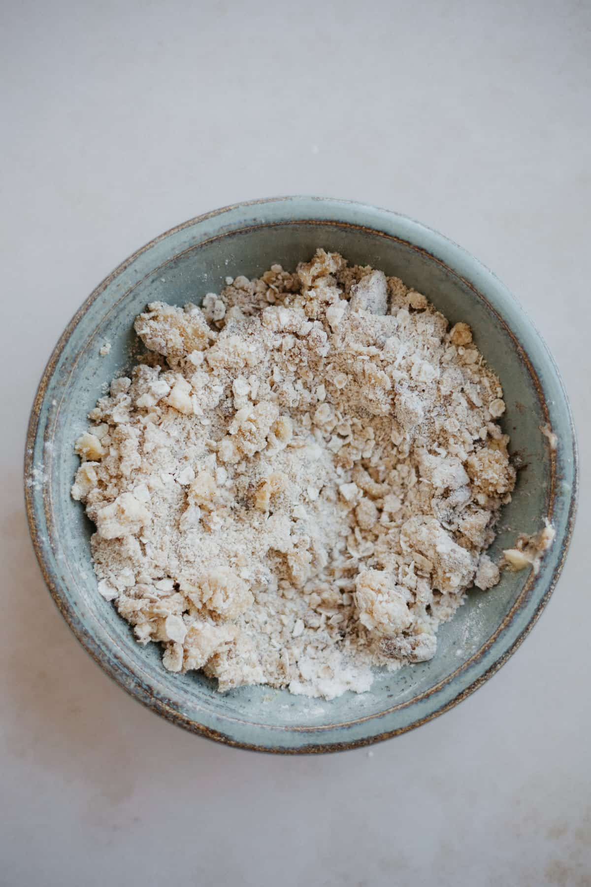 a small ceramic bowl with an oat crumble topping