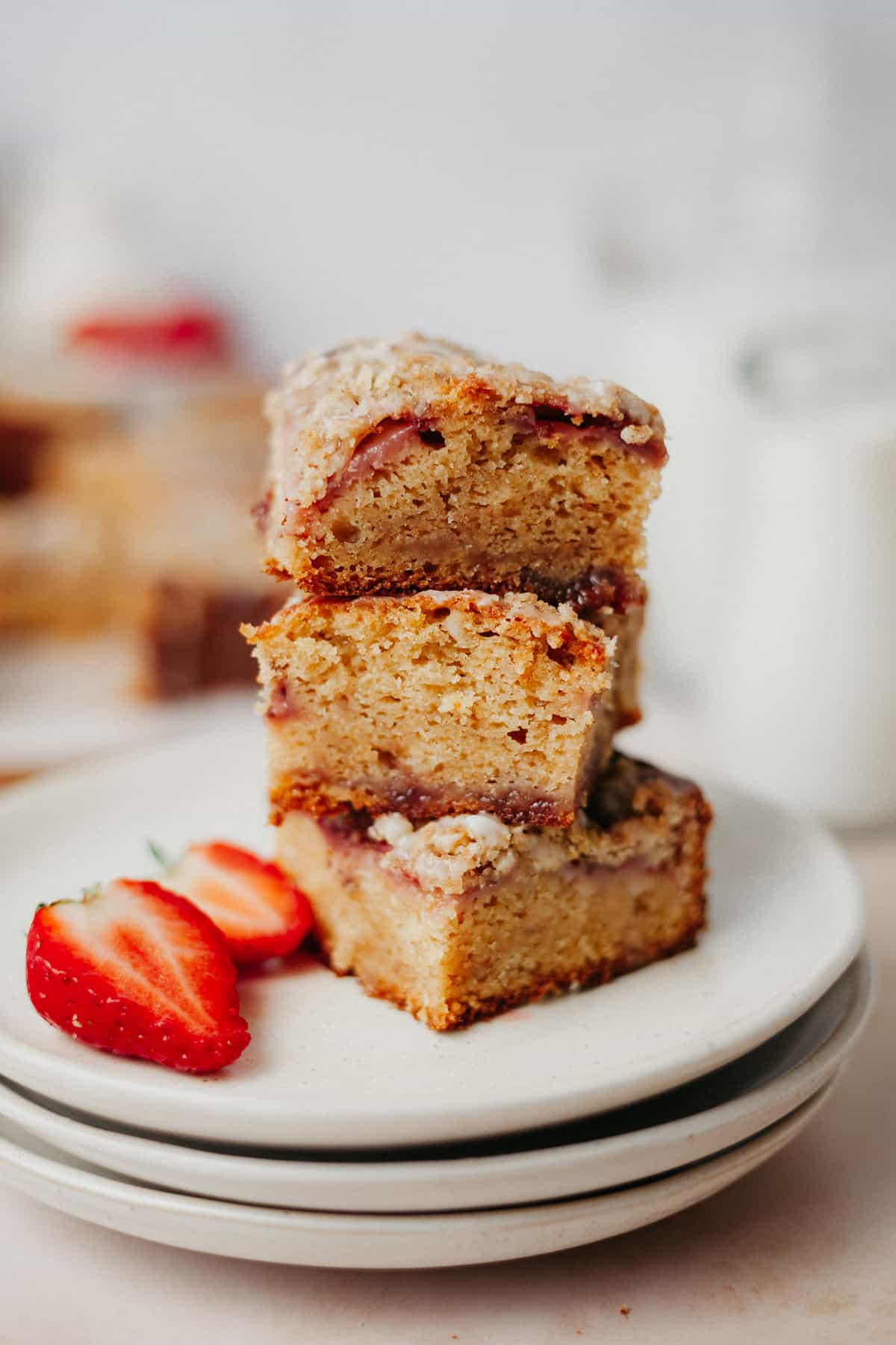 Three slices of strawberry crumble cake stacked on top of each other. It is on top of a small stack of beige plates