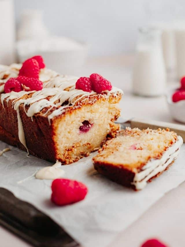 A raspberry and white chocolate loaf cake topped with white chocolate drizzle and fresh raspberries. One slice is cut.