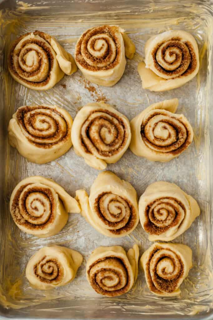 A silver pan with 12 unbaked cinnamon rolls