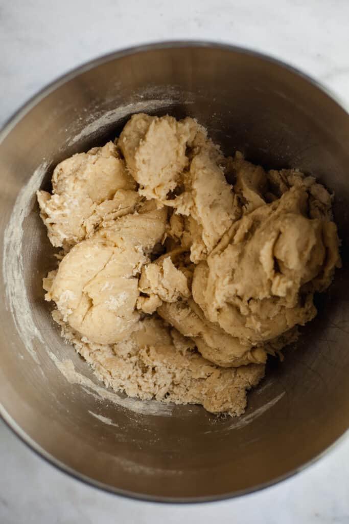 brioche dough in a silver mixing bowl