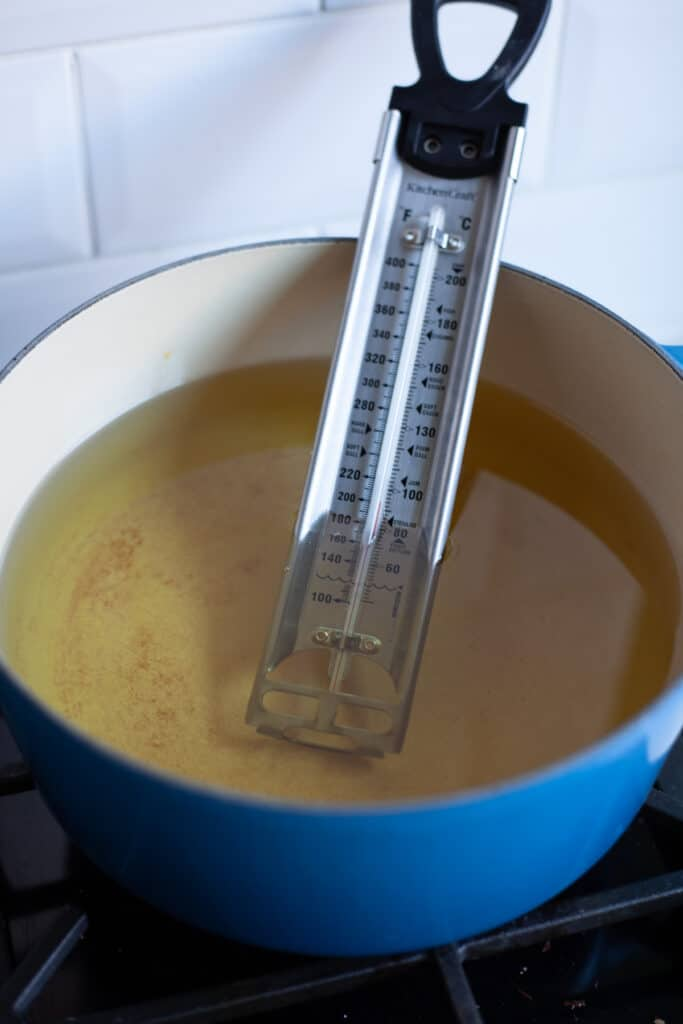 A heavy cast iron pan filled with oil, there is a thermometer in the oil.