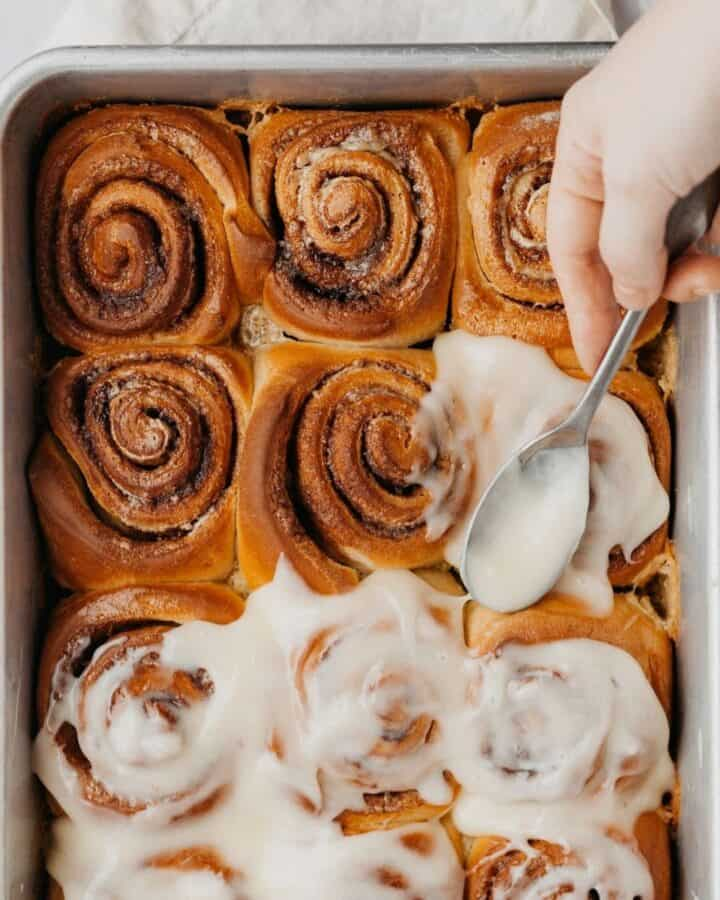 A close up of cinnamon rolls covered in cream cheese frosting, there is a hand holding a spoon that is icing the buns with the frosting