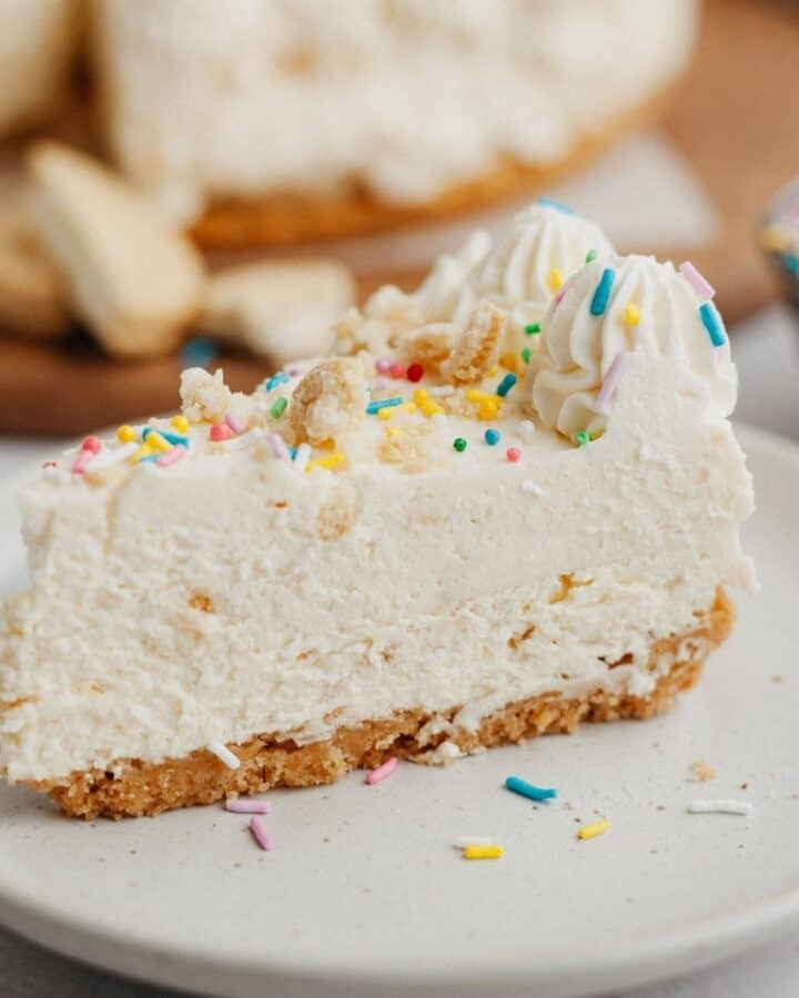 A slice of no bake cheesecake covered in rainbow sprinkles on a small beige plate