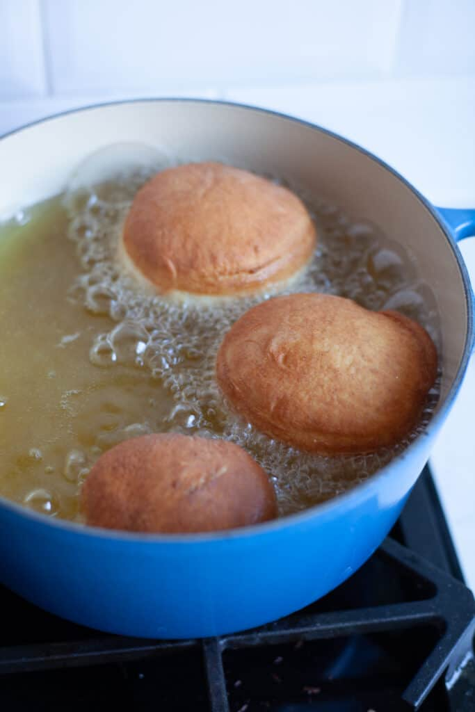 A large cast iron casserole dish, filled with hot oil. Three doughnuts are frying in it