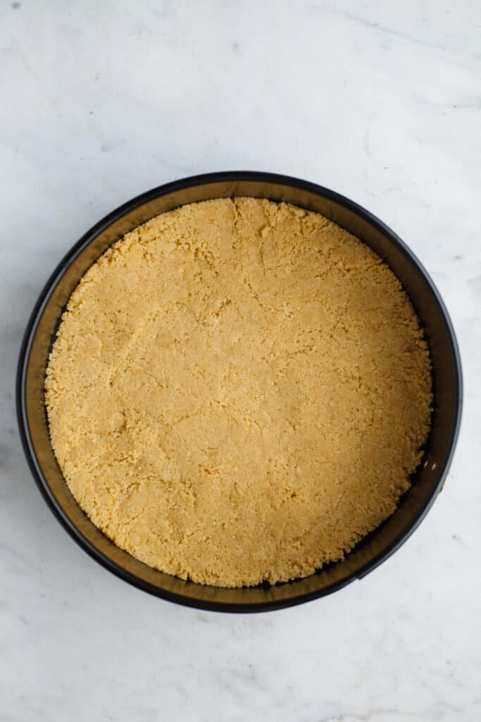 A springform pan with an unbaked golden oreo cheeescake crust