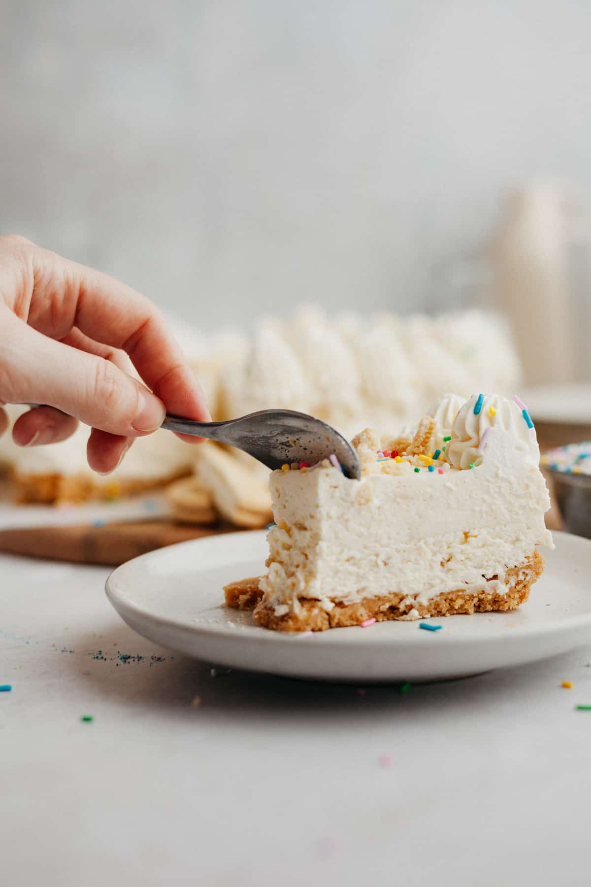 A slice of no bake cheesecake covered in rainbow sprinkles on a small beige plate. A hand is holding a small silver spoon and is cutting into the slice