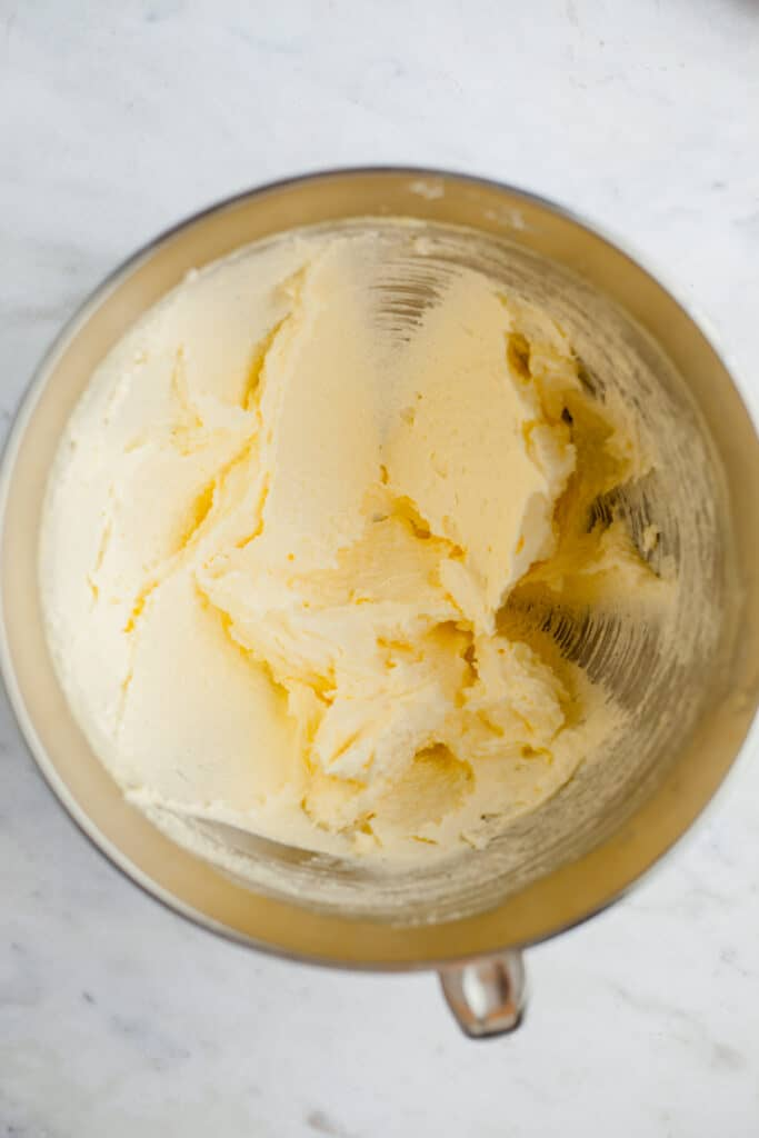 A silver mixing bowl with creamed butter and sugar