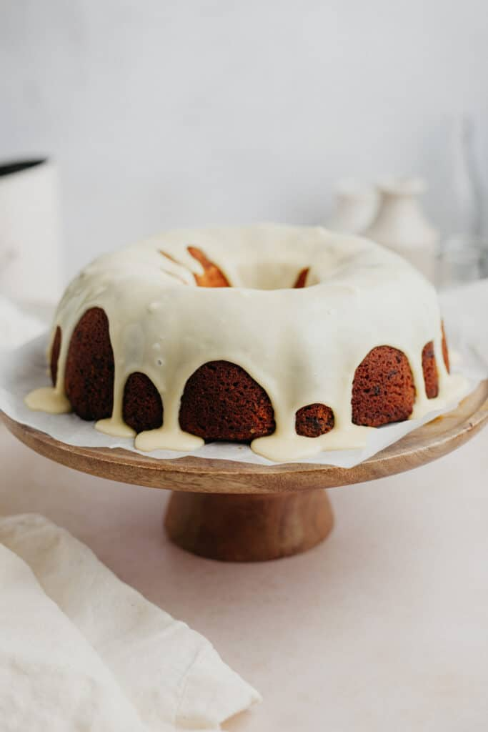 A bundt cake covered in white chocolate ganache on a wooden cake stand