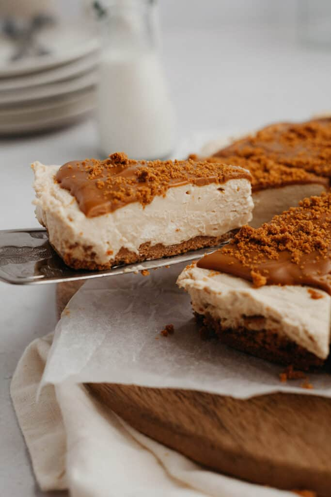 A slice of biscoff cheesecake being lifted out with a silver serving knife