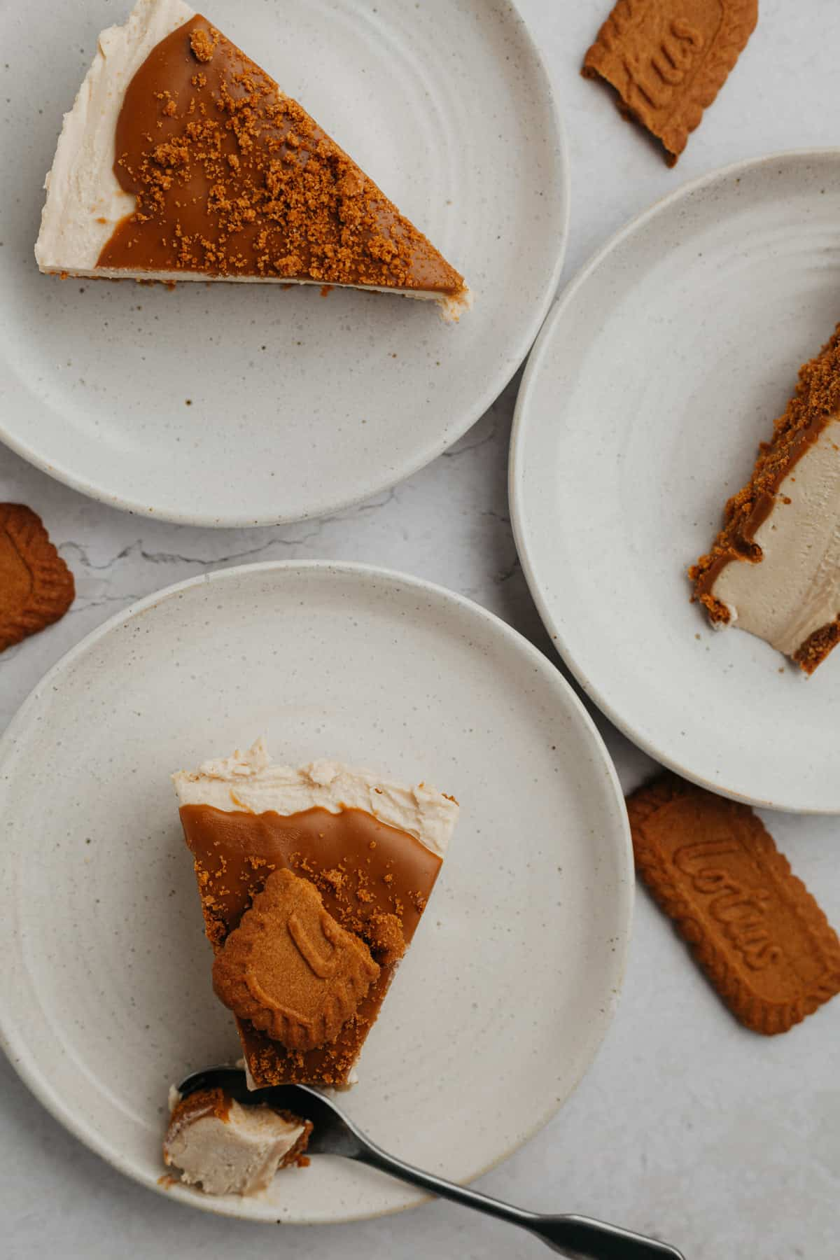 Three small plates, each one has a slice of biscoff cheesecake