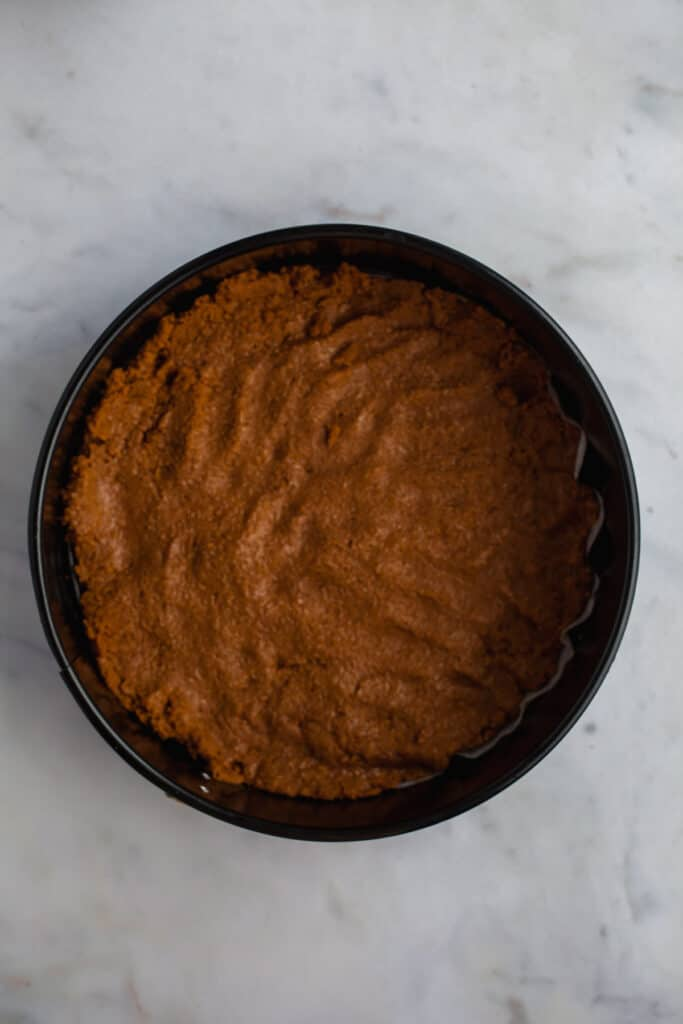 springform pan with biscoff cookie cheesecake crust