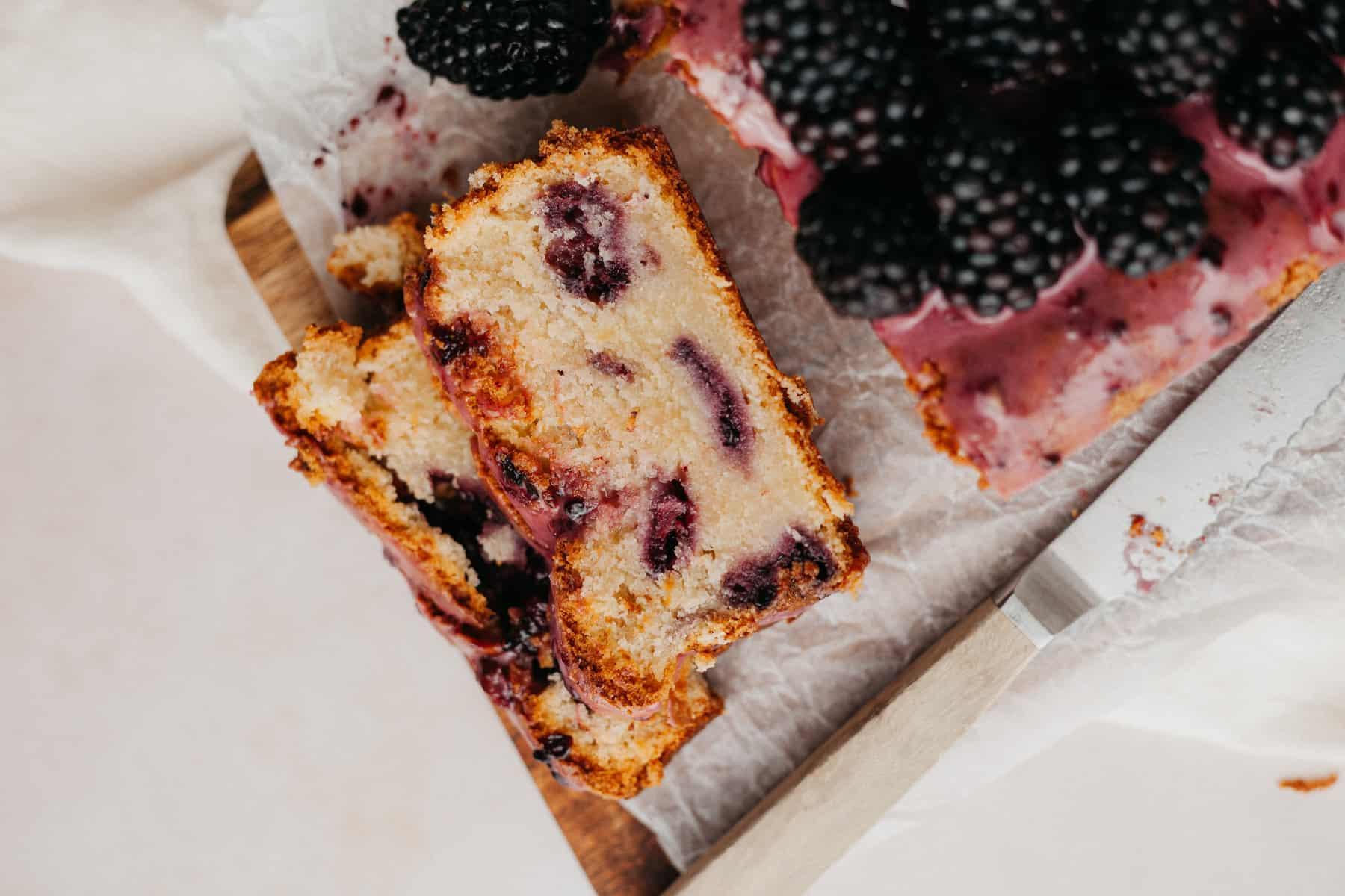 An overhead shot of two slices of blackberry lemon bread