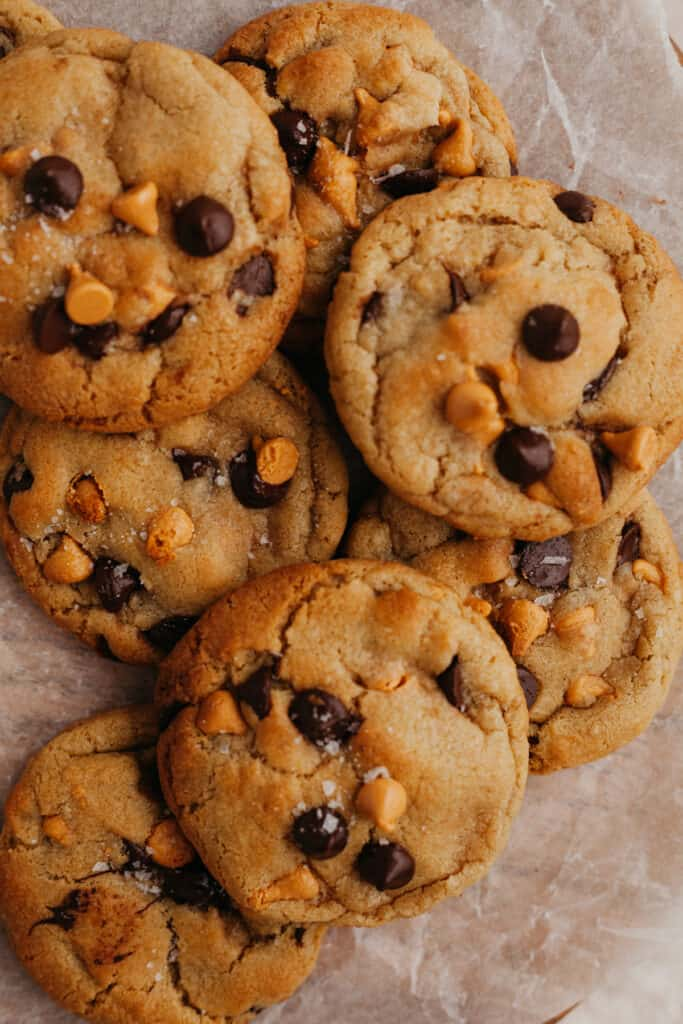 a pile of chocolate chip butterscotch cookies on parchment paper